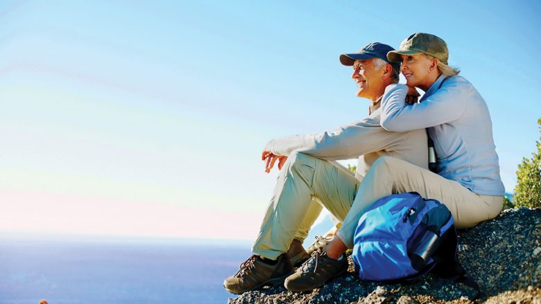 Couple sitting on mountainside relaxing after making STNL Property Investments